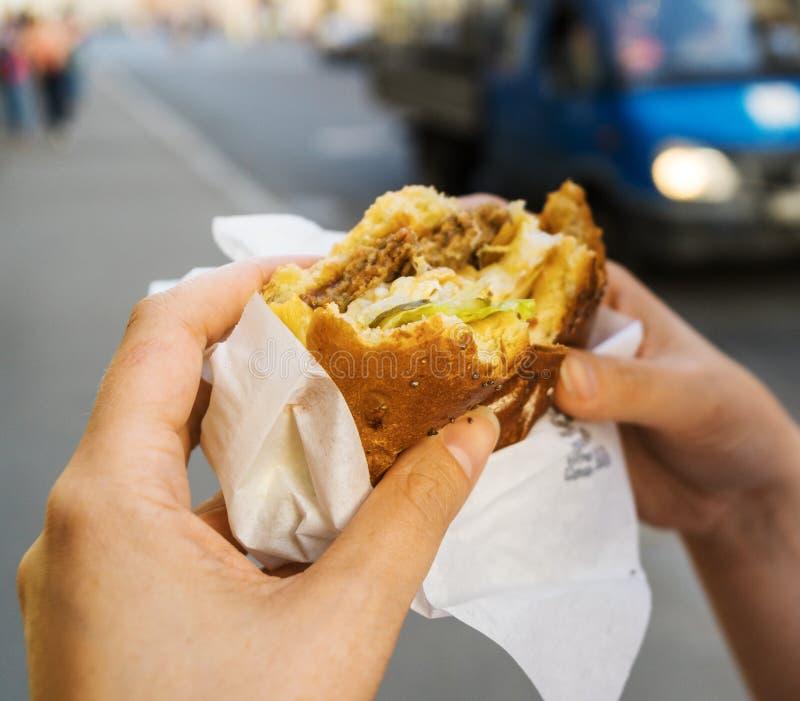Hamburger. Woman eating a hamburger on the street stock images