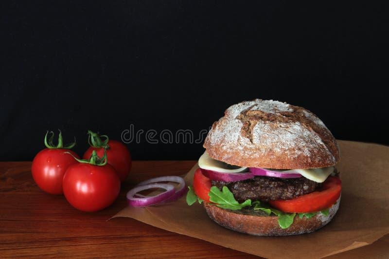 Hamburger z żyto babeczką na drewnianej powierzchni, czarny tło obrazy stock