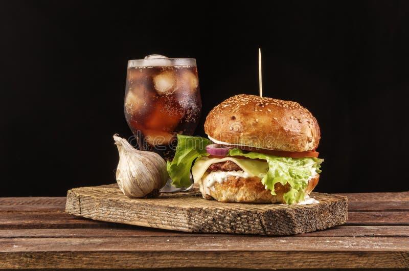 Hamburger z czosnkiem i kolą na drewnianej tnącej desce z copyspace obraz stock