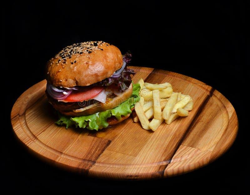 Hamburger z francuzem smaży na drewnianej desce Fast food fotografia stock