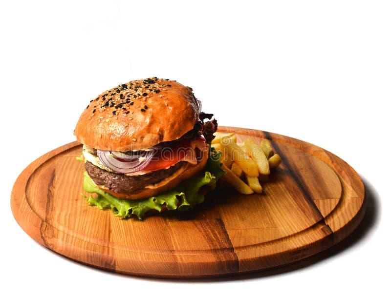 Hamburger z francuzem smaży na drewnianej desce Fast food odizolowywający na białym tle zdjęcie royalty free