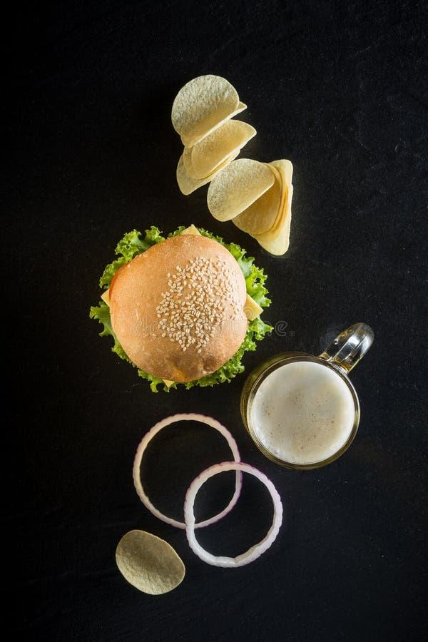 Hamburger z kubkiem zimny piwo, ketchup i crispy układy scaleni na d, fotografia stock
