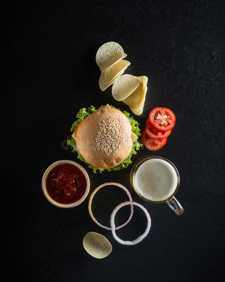 Hamburger z kubkiem zimny piwo, ketchup i crispy układy scaleni na d, zdjęcia stock