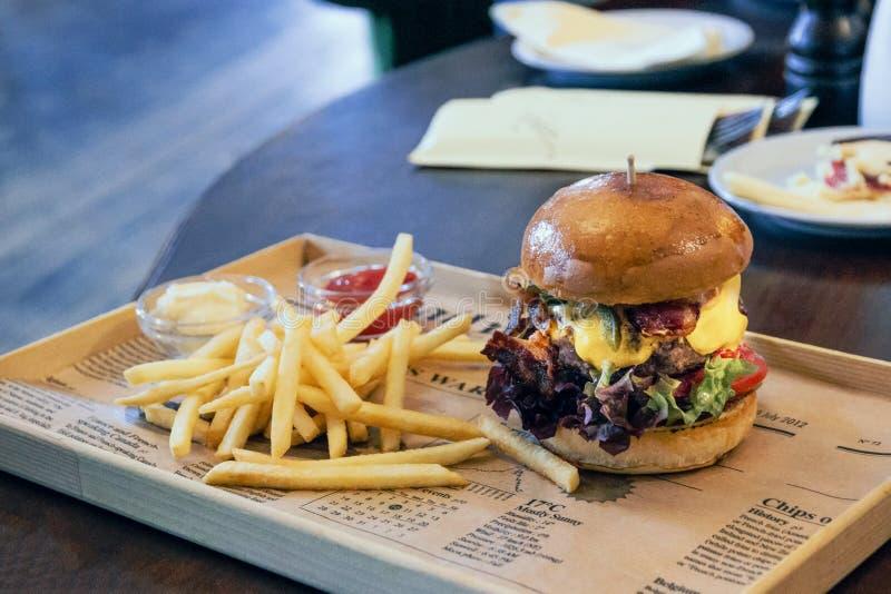 Hamburger z sałatą, bekon i francuz smaży na gazecie obraz royalty free