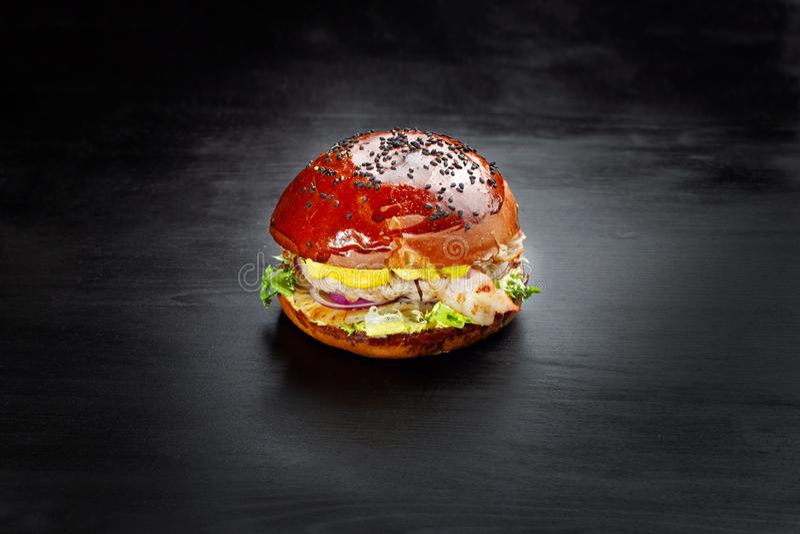 Hamburger z serem, stkiem, cebulkowymi pierścionkami, sałatą, ananasem i bekonem, obraz royalty free