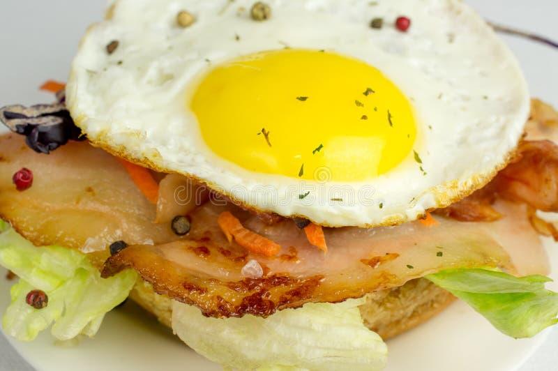 Hamburger z smażącym bekonem i jajkami zdjęcie stock