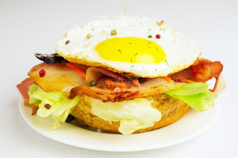 Hamburger z smażącym bekonem i jajkami fotografia stock