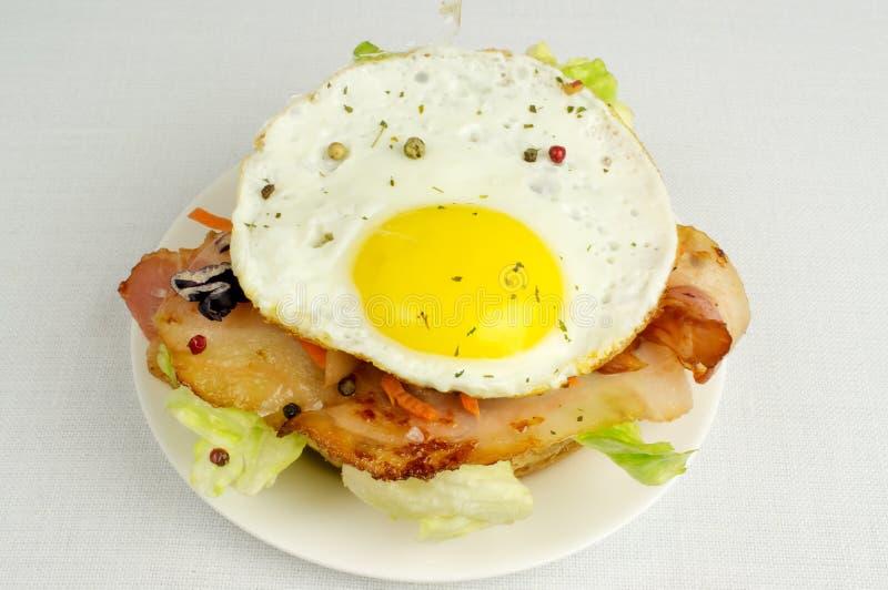 Hamburger z smażącym bekonem i jajkami obrazy stock