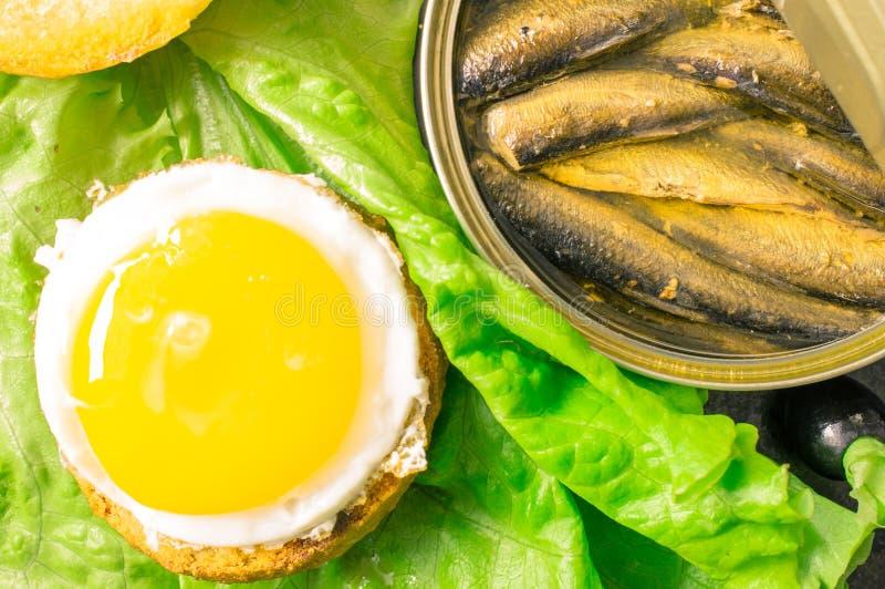Hamburger z smażącym jajkiem i sardynkami zdjęcia stock