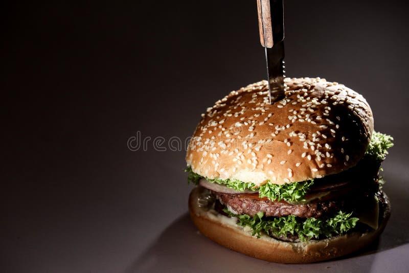 Hamburger z warzywami i mięsem Babeczka z sezamem Hamburger z nożem w nim zdjęcie stock