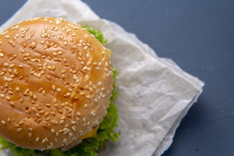 Hamburger z wołowina pasztecikiem, sałatką, plasterkiem, cebulami i kumberlandem z papryką w piec na grillu babeczce z sezamem, p obraz royalty free