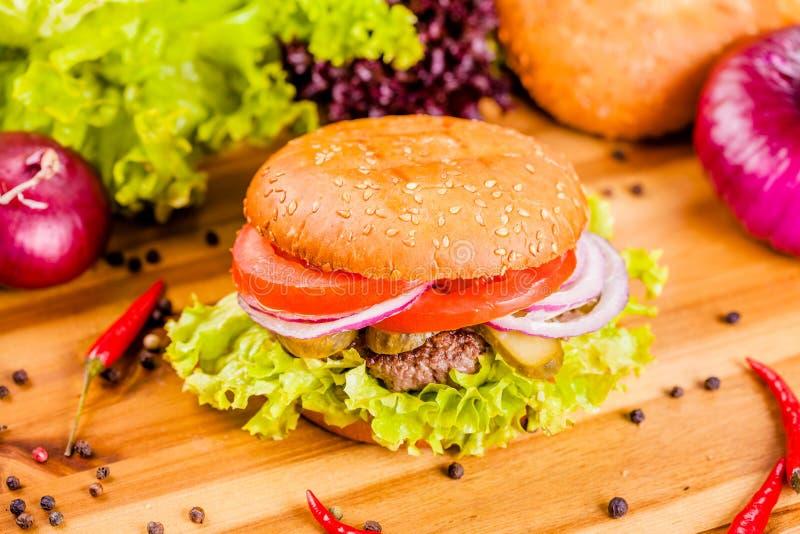 Hamburger z wołowiny cutlet, pomidorami i cebulkowymi pierścionkami na drewnianej desce, fotografia stock