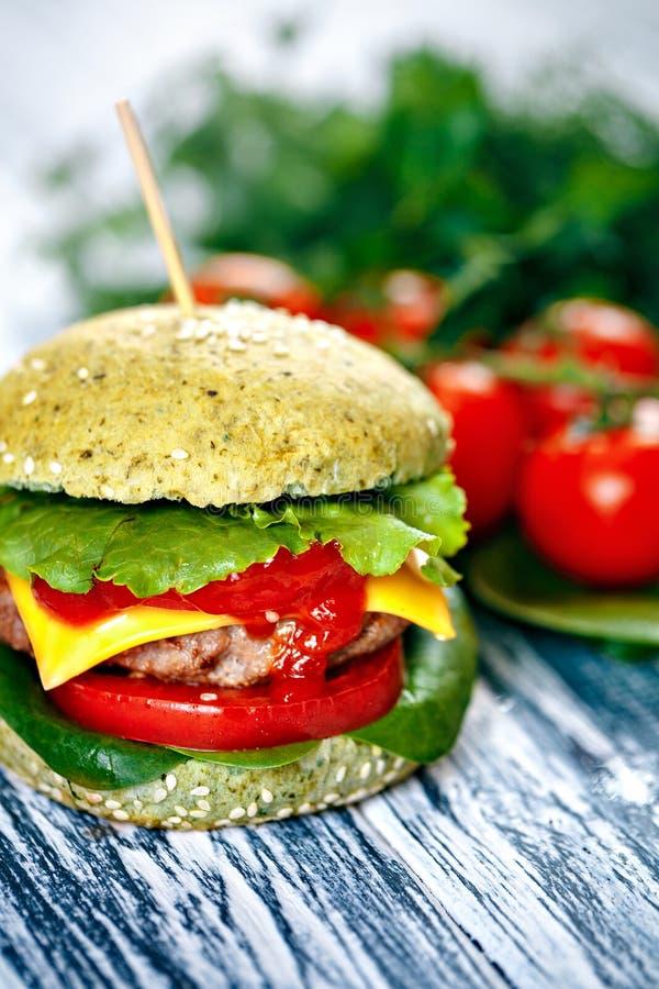 Hamburger z zieloną babeczką i świeżymi warzywami obraz stock