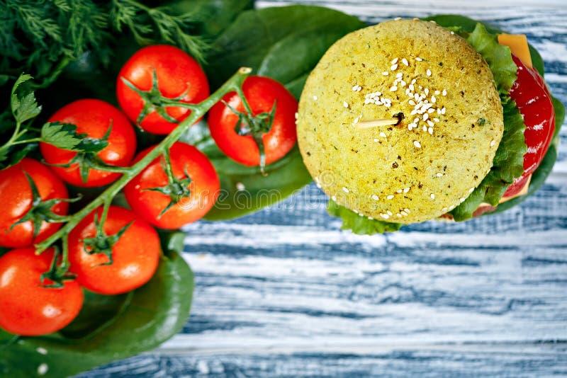 Hamburger z zieloną babeczką i świeżymi warzywami fotografia royalty free