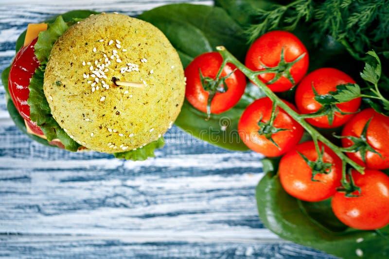 Hamburger z zieloną babeczką i świeżymi warzywami fotografia stock