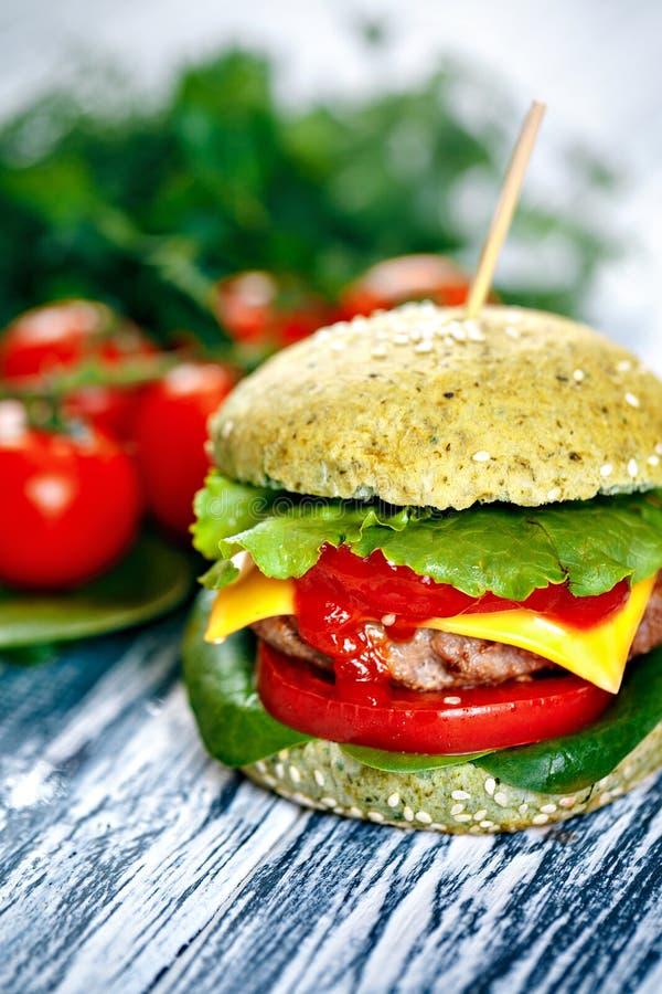 Hamburger z zieloną babeczką i świeżymi warzywami zdjęcia royalty free