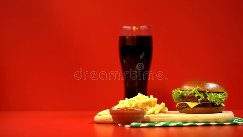 Hamburgerfrieten en ketchup op rode achtergrond, hoge caloriemaaltijd worden geïsoleerd die stock foto's