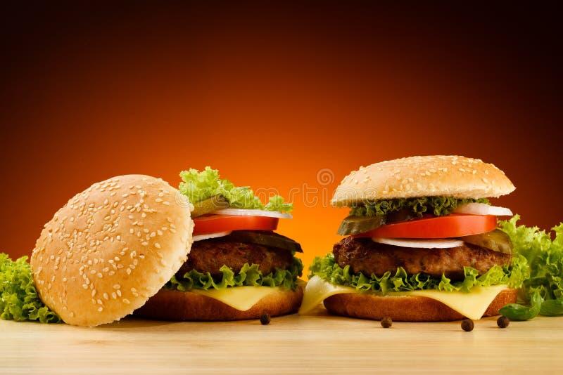 Hamburgers. Big cheeseburgers and fresh vegetables royalty free stock photo