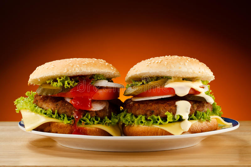 Hamburgers. Big cheeseburgers and fresh vegetables royalty free stock photo
