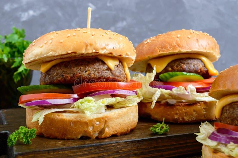 Hamburgers avec la côtelette juteuse, légumes frais, petit pain croustillant avec les graines de sésame sur une table en bois Pla photos stock