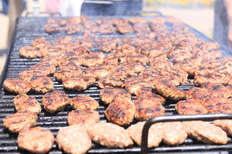 Hamburgers on barbeque. Hamburgers cooking on barbeque grill and hot smoke stock photography