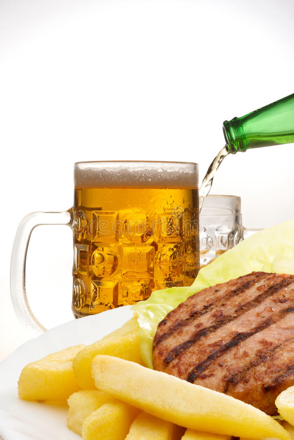 Hamburgers and chips with beer stock photography
