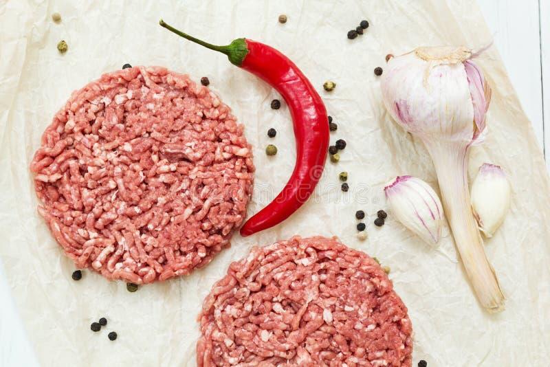 Hamburgers crus juteux faits à partir de la viande organique sur un fond en bois blanc avec des épices Vue sup?rieure image stock