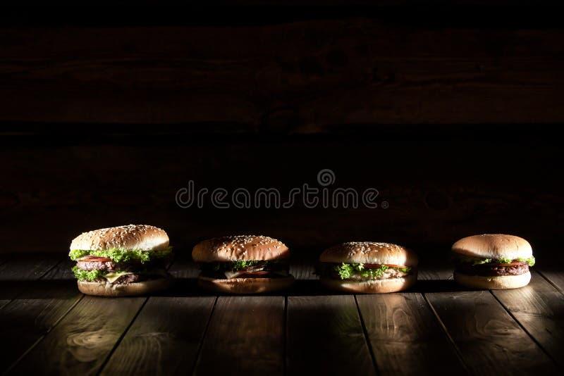 Hamburgers délicieux frais avec de la viande, les légumes et la feuille de salade placée sur un fond en bois dans une rangée photos stock