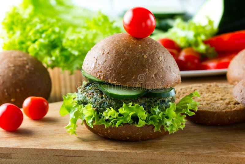 Hamburgers d'épinards de Vegan avec du pain, le concombre et la laitue de seigle photos stock