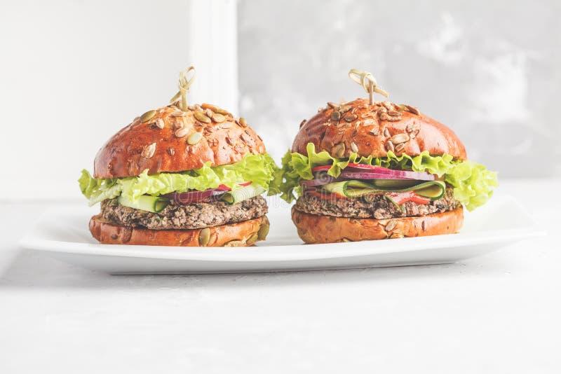 Hamburgers de haricot de Vegan avec la sauce de légume et tomate sur le DIS blanc image libre de droits