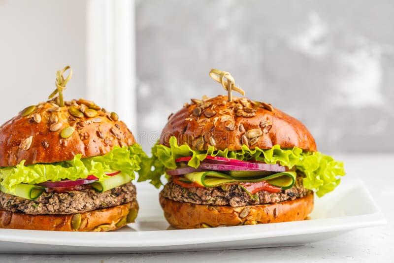 Hamburgers de haricot de Vegan avec la sauce de légume et tomate sur le DIS blanc images stock
