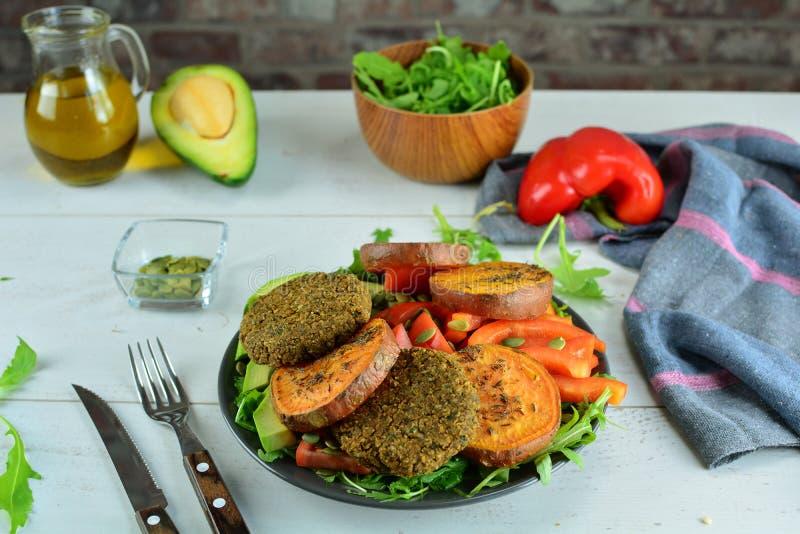 Hamburgers de lentille avec de la salade cuite au four de patate douce et d'avocat avec l'Arugula, les poivrons et les tomates images stock