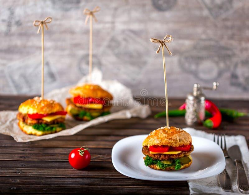 Hamburgers en vissen op een houten lijst royalty-vrije stock afbeelding