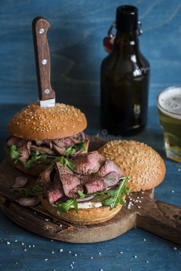 Hamburgers et bières faits maison de boeuf de bifteck photo libre de droits