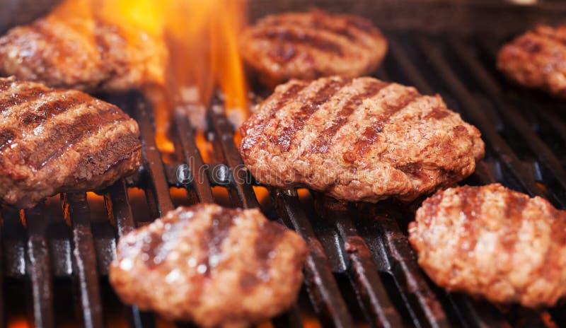 Hamburgers faisant cuire sur le gril photographie stock libre de droits