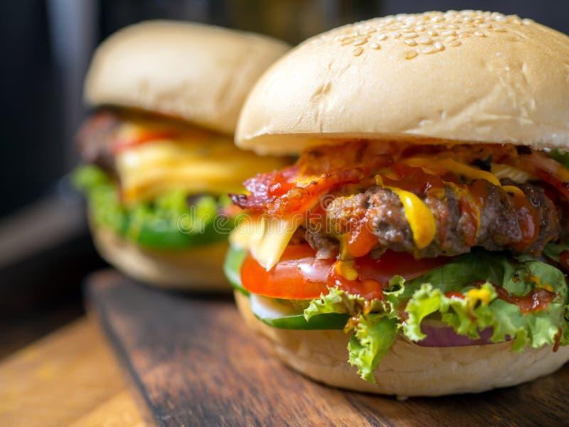 Hamburgers faits maison avec de la bière et le kola faits de lard, porc, tomate, laitue, oignon, fromage et épices sur le fond en images libres de droits