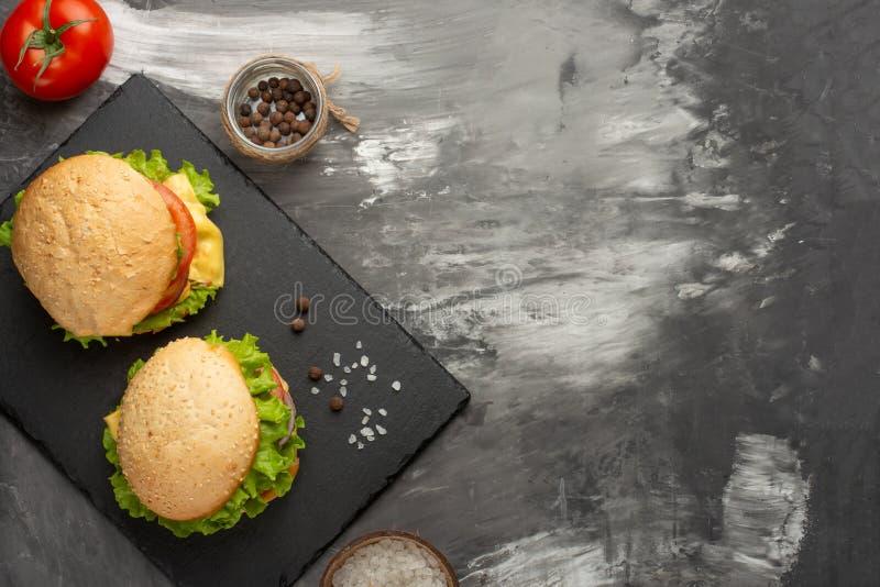 Hamburgers faits maison délicieux, hamburgers avec du boeuf, fromage, tomates, et salade Vue supérieure avec l'espace de copie image libre de droits