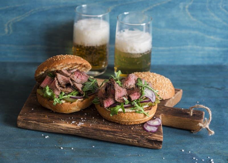 Hamburgers faits maison de boeuf de bifteck et deux bières en verre images libres de droits