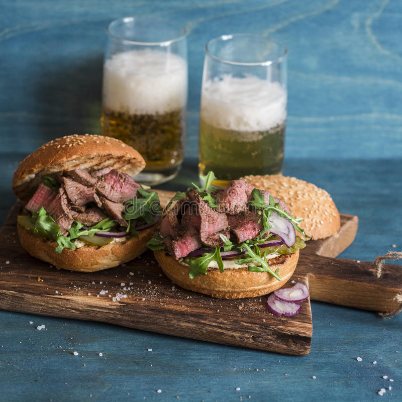 Hamburgers faits maison de boeuf de bifteck et deux bières en verre image stock
