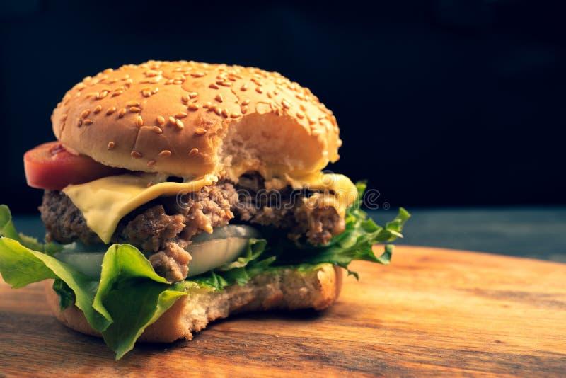 Hamburgers faits maison frais, légumes frais délicieux, laitue, tomates, fromage qui sont mordues sur une planche à découper, l'e image libre de droits