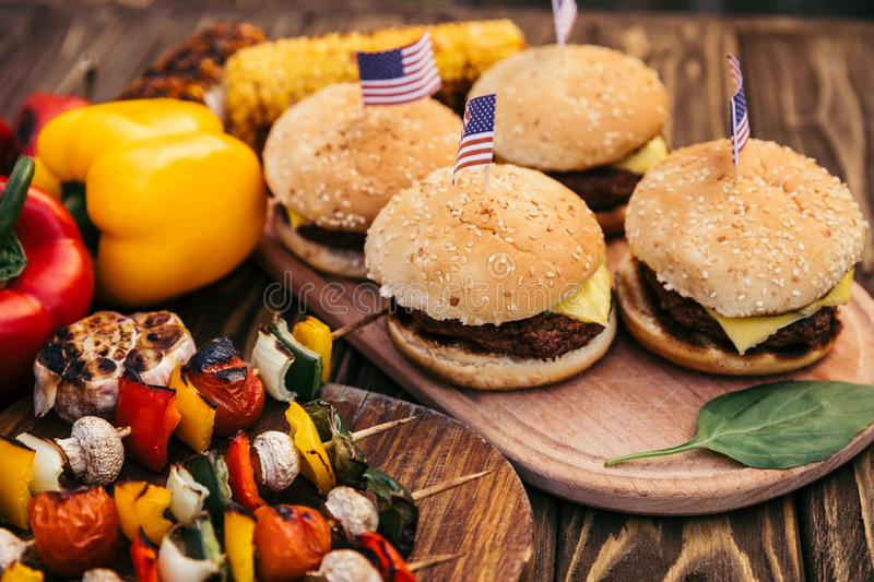 Hamburgers with flags and vegetables cooked outdoors on grill stock images