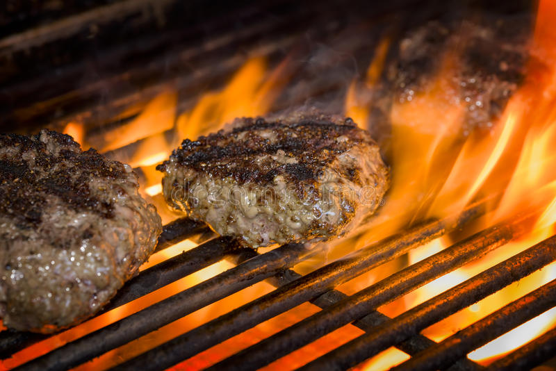 Hamburgers on a Flaming Grill royalty free stock images