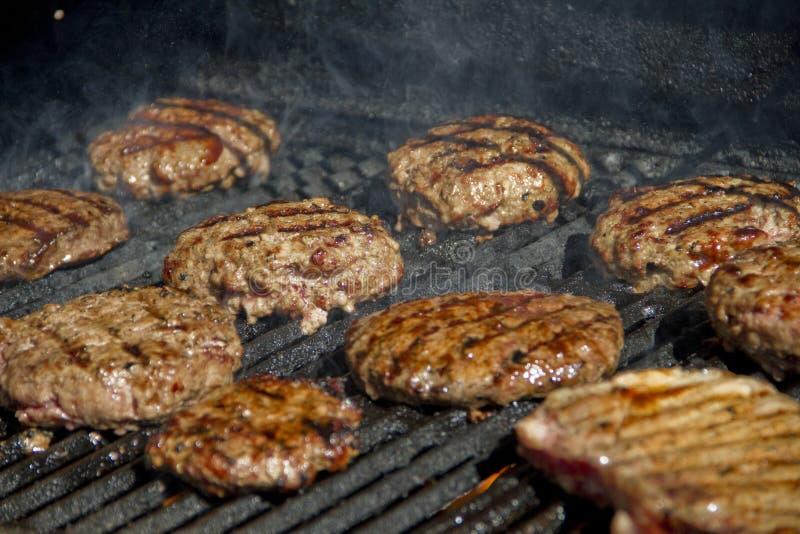 Hamburgers on a grill stock photos