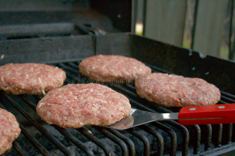 Hamburgers on a grill royalty free stock photos