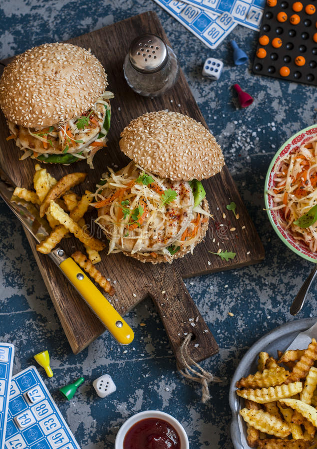 Hamburgers with grilled chicken and cole slaw on a wooden board on the table with cards and bingo chips, top view. royalty free stock photo