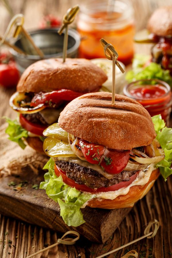 Hamburgers, homemade burgers with grilled buns with addition of addition of beef cutlet, lettuce, tomato,pickled cucumber, grille royalty free stock photography