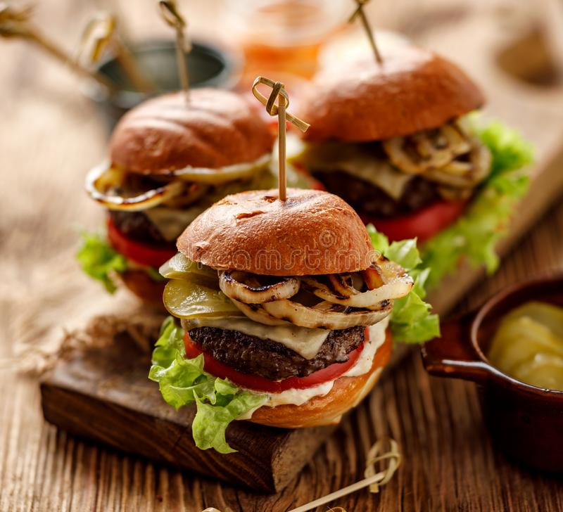Hamburgers, homemade burgers with grilled buns with addition of addition of beef cutlet, lettuce, tomato,pickled cucumber, grille stock images