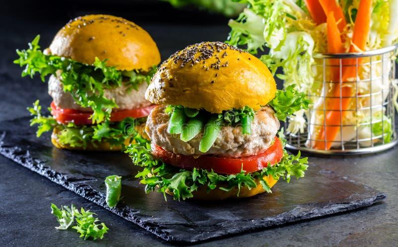 Hamburgers jaunes colorés Hamburgers d'hamburgers de poulet avec du pain de safran des indes photo stock