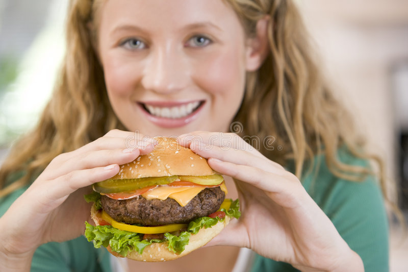 hamburgers mangeant la fille d'adolescent photo libre de droits