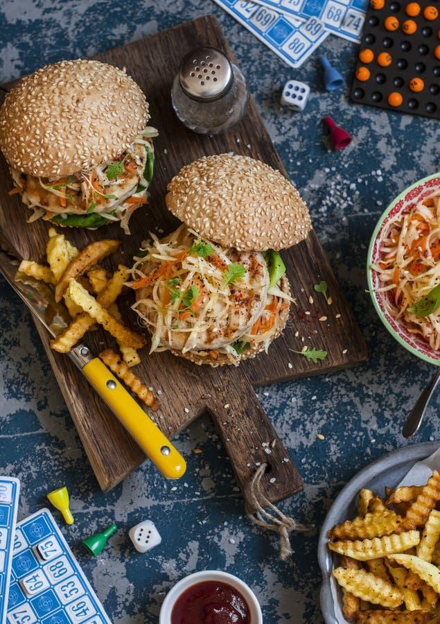 Hamburgers met geroosterde kip en cole slaw op een houten raad op de lijst met kaarten en bingospaanders, hoogste mening royalty-vrije stock foto
